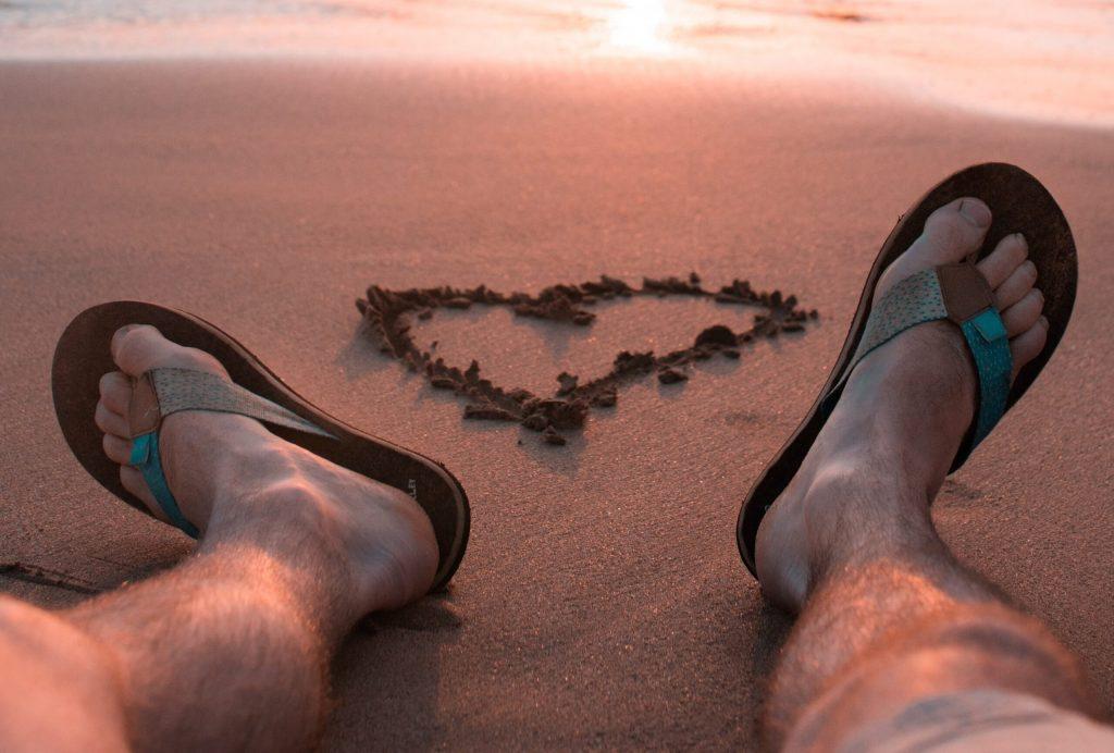 man feet wearing flip flop sitting beach side