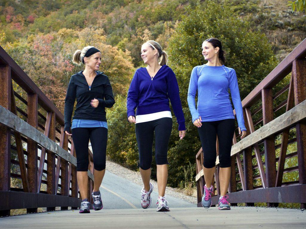 3 women wearing lightweight walking shoes and walking on the road