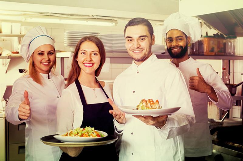 hotel/restaurant kitchen staff including men women both in  in uniform holding some food
