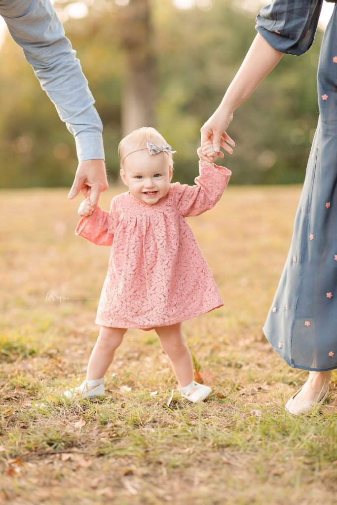 A baby girl trying to learn walking holding her parents fingers wearing walking shoes