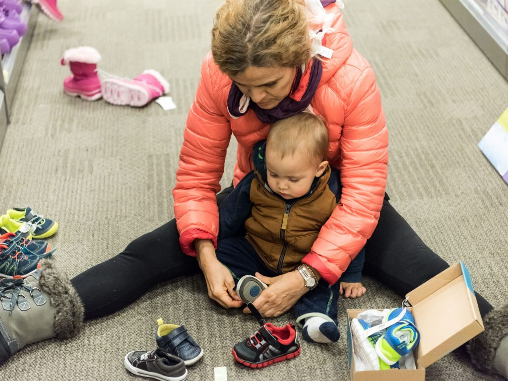 A women sitting with her kid and trying to wear shoes to her kid